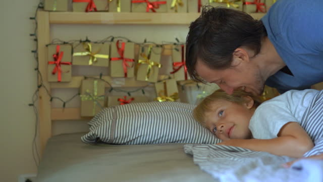 Slowmotion shot offather waking up his little son. He wakes up the boy and shows him an advent calendar that he had made by himself. Getting ready for Christmas and New Year concept. Advent calendar concept