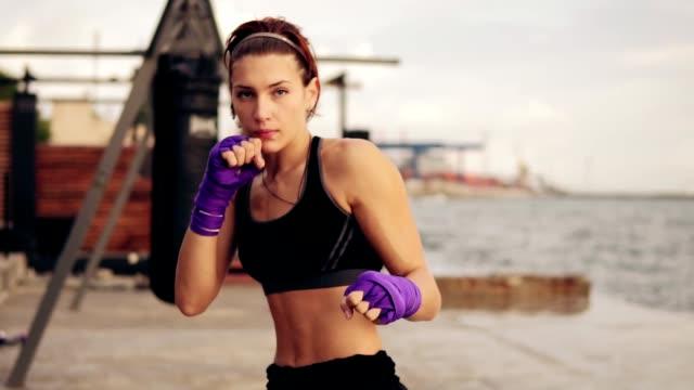 vídeos de stock, filmes e b-roll de slowmotion tiro: boxe sombra de mulher jovem com suas mãos envolvida em fitas de boxe roxo, olhando para a câmera. linda boxer feminino formação na praia pela manhã - autodefesa