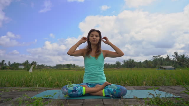 slowmotion steadicam shot of a young woman doing meditation for muladhara chakra in a balinese way - mudra video stock e b–roll