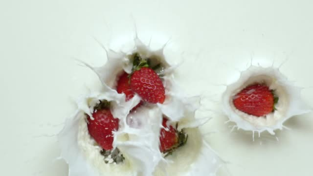 slow-motion: strawberry pile falling into milk. - bacca video stock e b–roll