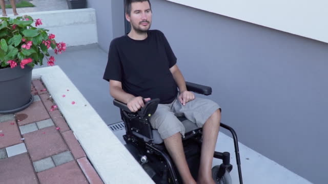 Slowmotion video of a man in a electric wheelchair using a ramp at accessible house