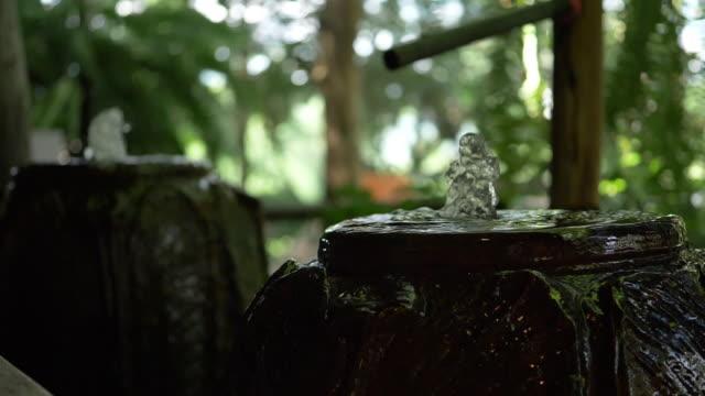 Slow-motion, water jar fountain in green garden