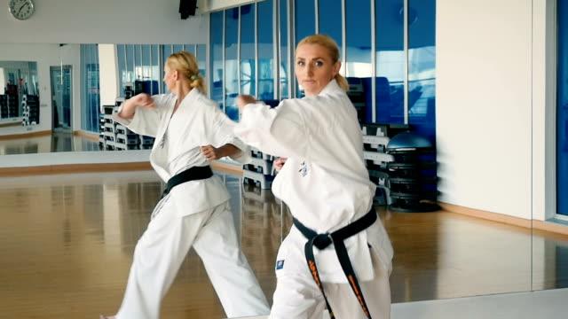 vídeos y material grabado en eventos de stock de el truco de karate de la mujer de slowmotion cerca del espejo en el gimnasio - kárate