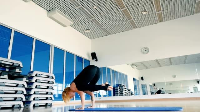 slowmotion: junges mädchen, das yoga im zentrum des sports praktiziert - haarfarbe stock-videos und b-roll-filmmaterial