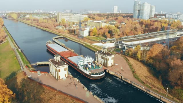 sluice gates on the river. aerial view barge, ship in the river gateway. the movement of ships and barges along the canal through the river gateway in autumn sunny day. - chiatta video stock e b–roll