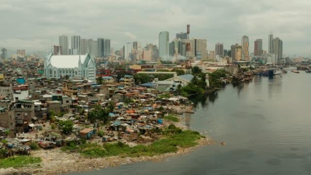 slumsy biednych ludzi na tle dużego miasta. miasto manila, biedne i ubogie obszary - państwo lokalizacja geograficzna filmów i materiałów b-roll