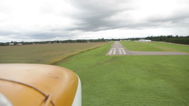 Small Airplane Landing on a Rural Airport Runway A small airplane making a final approach and landing on a runway at a rural airport. airfield stock videos & royalty-free footage
