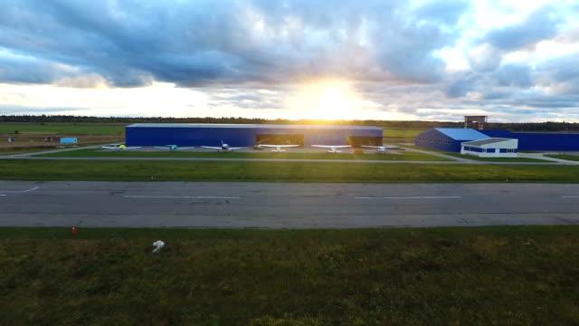 małe samolotów w pobliżu hangar o zachodzie słońca - mały filmów i materiałów b-roll