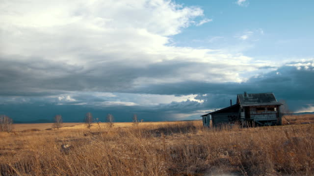 Small alone house against the cloudy sky in the spring field, time-lapse video
