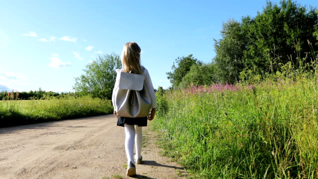 Una chica rubia hermosa Escuelita va a la escuela en el camino de arena a través del campo. - vídeo