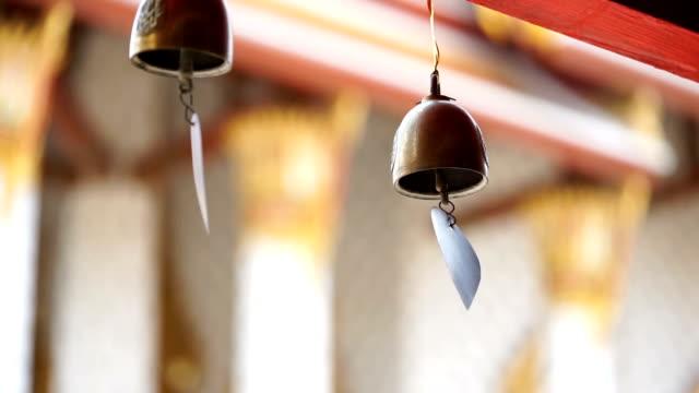 Small bell hangs around corridor around church in Thai temple video