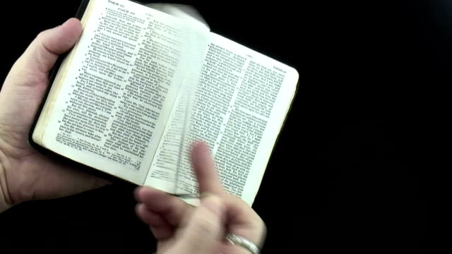 Small Bible Opening a small black covered Bible against a black background old testament stock videos & royalty-free footage