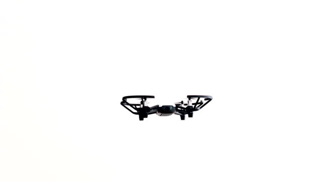 A small black and white drone stationed in the air in hovering on a white background. A small black and white drone stationed in the air in hovering on a white background. Some small movements to the left and right to improve stability. hovering stock videos & royalty-free footage