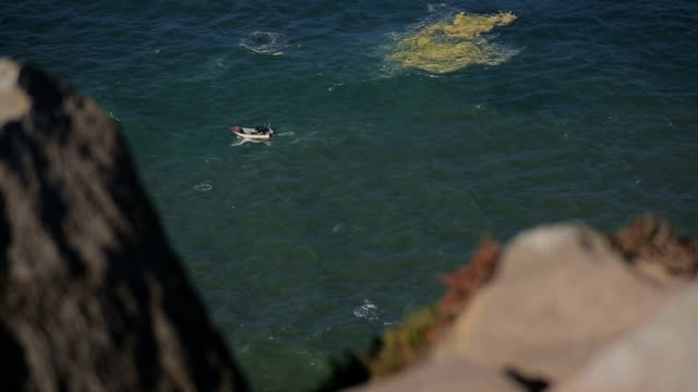 Small boat at the foot of rocks and cliffs at Cabo da Roca Portugal, stormy weather video