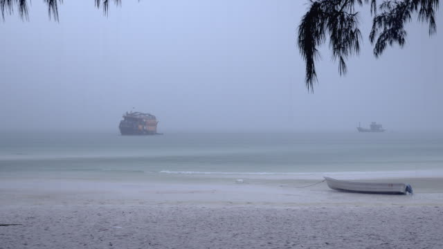 Small boat on a sand beach under heavy rainfall and Cruise ship reaching the shore in the background video