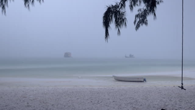 Small boat on a sand beach under heavy rainfall and tree swing in the foreground video