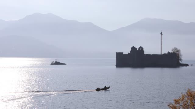 vídeos de stock e filmes b-roll de small boat plys waters in front of castle, near shoreline - lago maggiore