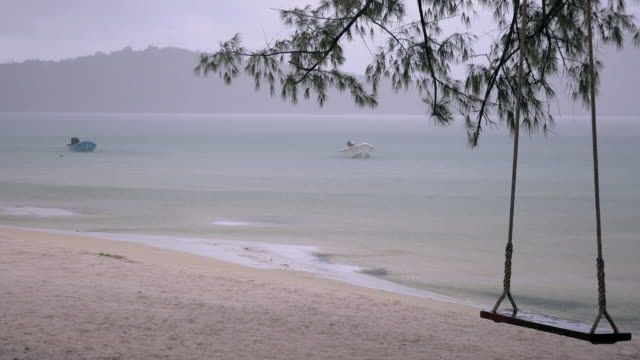 Small boats anchored in shallow waters under heavy rainfall and tree swing in the foreground video
