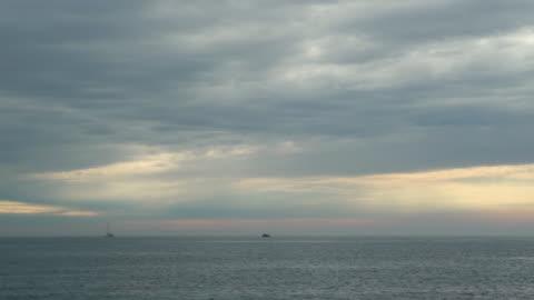 małe łodzie na morzu w pochmurny dzień - horyzont wodny filmów i materiałów b-roll