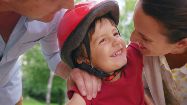 SLO MO Small boy getting kisses from his mother while wearing a bike helmet Slow motion medium shot of a little boy wearing a helmet while sitting on his bike and his mom gives him a kiss. Shot in Slovenia. shirt stock videos & royalty-free footage