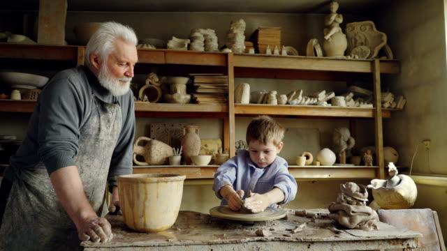 small boy is molding clayware in his grandfathers's studio while his caring senior grandpa is standing near him and watching him with love. family traditions concept. - hobby filmów i materiałów b-roll