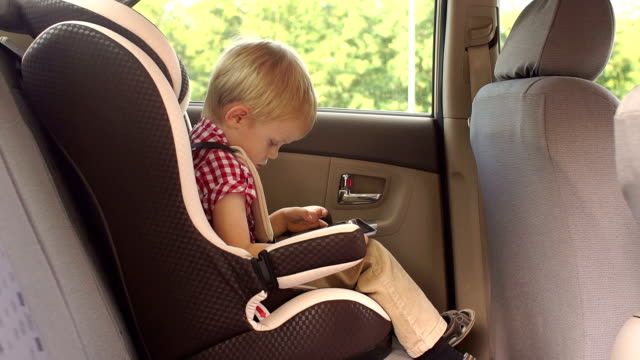 A small boy of five years is sitting in a car seat in a car and playing a tablet A small blonde boy of five years is sitting in a car seat in a car and playing a tablet. Slow motion. Close-up seat stock videos & royalty-free footage