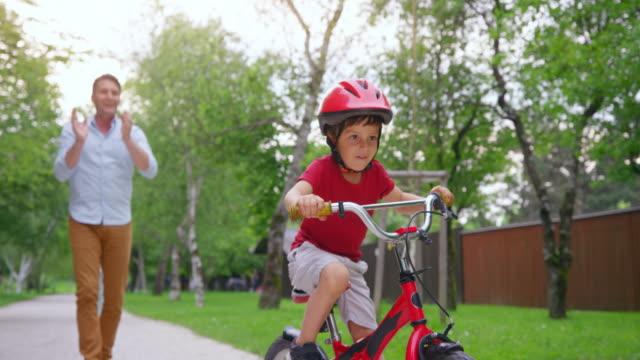 slo mo piccolo ragazzo sulla sua bicicletta in sella per la prima volta e padre applaudendo con entusiasmo - carrellata video stock e b–roll