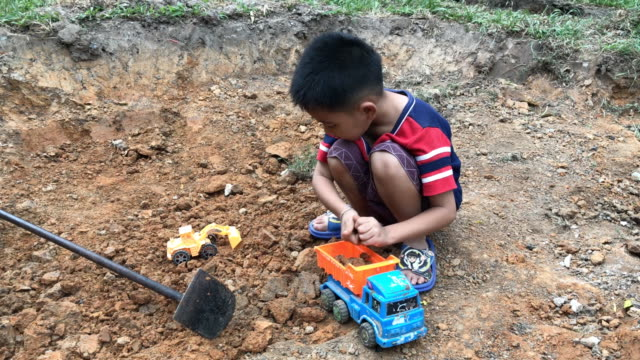 Small boy playing his toy plastic dump truck with rocks