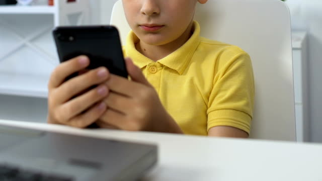Small boy sitting in front of laptop, watching video on smartphone, addiction