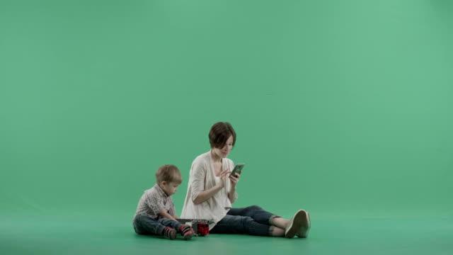 vídeos y material grabado en eventos de stock de niño sentado al lado de su madre intenta llamar su atención pero ella no responde - árboles genealógicos