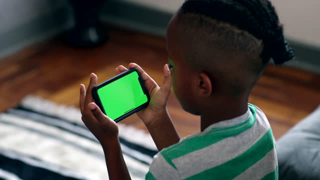 Small boy watching content on phone. Green screen mock-up. African child holding smartphone