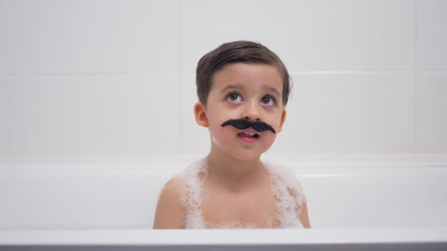petit garçon avec une moustache noire se trouve dans la salle de bains - Vidéo