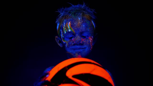 A small boy with UV patterns on his skin holding an orange glowing soccer ball