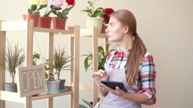Small business. A girl in a plaid shirt and a striped apron stands with a digital tablet in her hands and plans. Florist working with flowers in pots, believes after entering data into the gadget