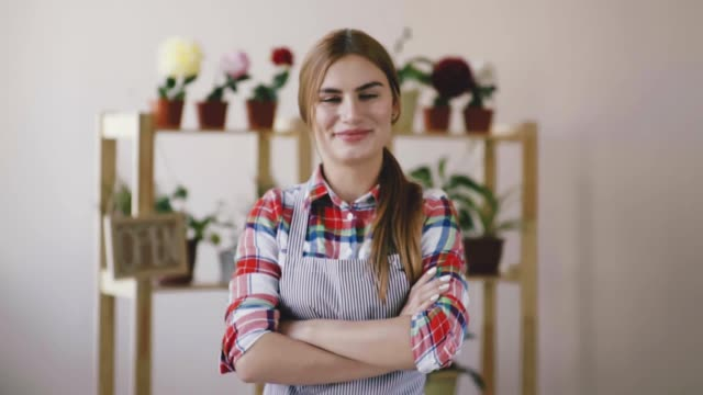 Small business. A girl in a striped apron and a plaid shirt stands in a flower shop and folds her hands on her chest. On the background of signs