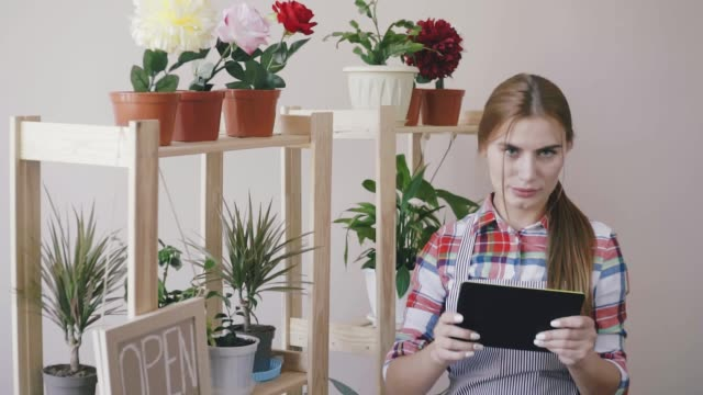 Small business. A girl in a striped apron and plaid shirt stands in a flower shop. On the shelves are flowers and an open sign. The florist girl stands near the shelf with flowers and plans with the help of a digital computer