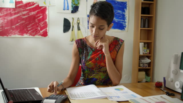 Small business, hispanic woman doing budget in fashion designer atelier video