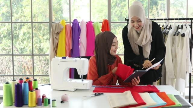 vídeos y material grabado en eventos de stock de pequeña empresa de mujer musulmana diseñadora de moda de trabajo y diseñador de moda dibujo ideas y bocetos interiores con vestidos en la tienda de ropa y sastrería - bocetos de diseños de moda
