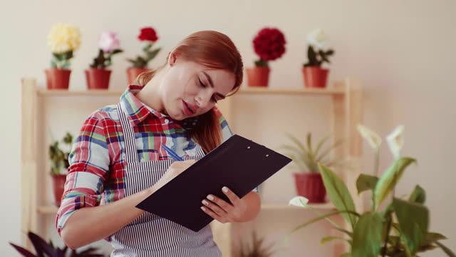 Small business. Opening a flower shop. A girl in a plaid shirt and a striped apron holding a paper tablet, smiling and talking to the client on the phone. In the background, shelves with flowers in pots