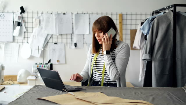 small business owner is ordering fabric for tailor's shop with mobile phone and working with laptop. woman is talking and typing simultaneously. modern means of communication concept. - owner laptop smartphone video stock e b–roll