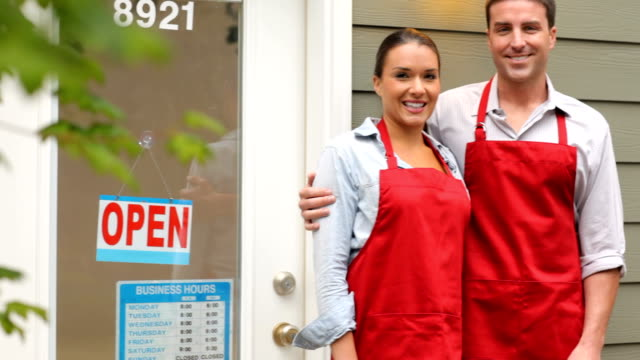 small business owners in front of shop - open sign stock videos & royalty-free footage