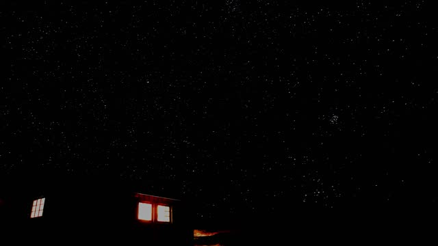 vídeos de stock e filmes b-roll de small cabin in the mountains with light shining out the windows and a starry night sky in the background. time lapse video. - isolated house, exterior