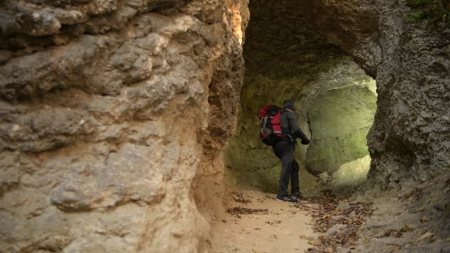 small cave exploring by caucasian hiker in his 30s. - кейвинг стоковые видео и кадры b-roll