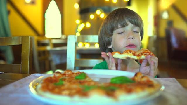 stockvideo's en b-roll-footage met een klein kind in een fastfoodcafé eet pizza - dikke pizza close up