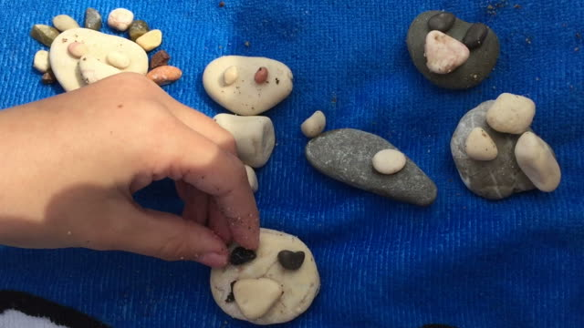 Small child laying out shingle pebbles on beach. Funny mugs are obtained from stones on beach. Smile symbol is background for vacation relax and calm. video
