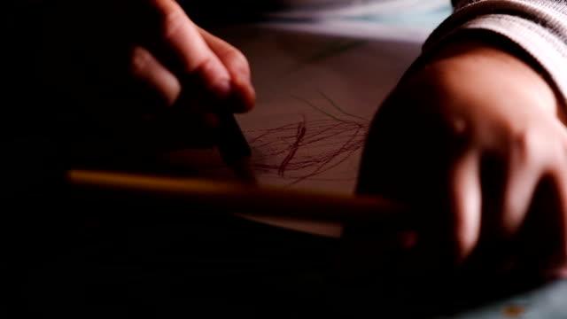 il bambino impara a disegnare con le matite su carta, al rallentatore - matita colorata video stock e b–roll