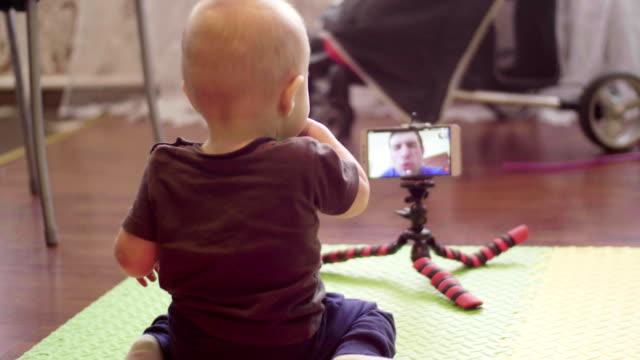 små barn sitter på golvet kommunicerar videosamtal i en smartphone med hans kaukasiska pappa. inomhus fullhd tillbaka visa filmen - 4 kilometer bildbanksvideor och videomaterial från bakom kulisserna