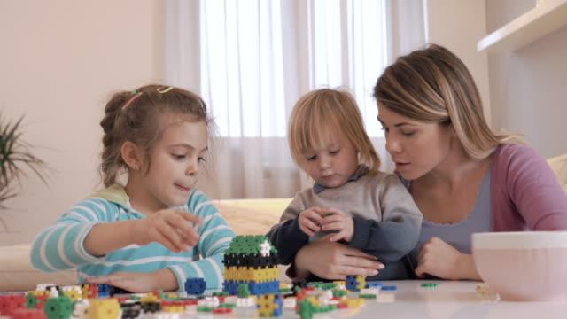 小さな子供と母親が自宅のパズルで遊ぶ。 ビデオ