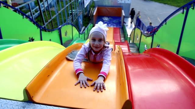 Small children ride a sliding board video