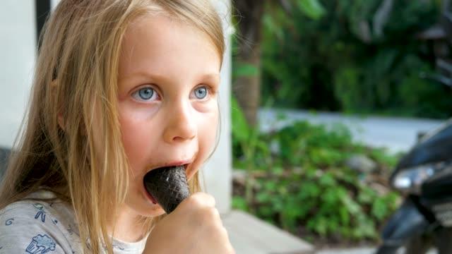 vídeos de stock e filmes b-roll de small cute blond girl with dirty mouth eats black chocolate ice-cream - boca suja